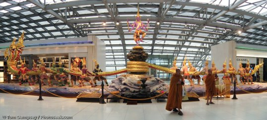 Buddhist monks admire the attractive sculpture of the Churning of the Milk Ocean, which measures about 30 meters wide and 5.5 meters high, too big for fire regulations, requiring it to be moved out of the Suvarnabhumi Bangkok airport in 2008. The Churning